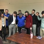Faculty and staff joined Dave Bechler in prayer when he announced he would be retiring.