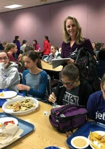 Radella Vrolijk, board member, visits with students during lunch