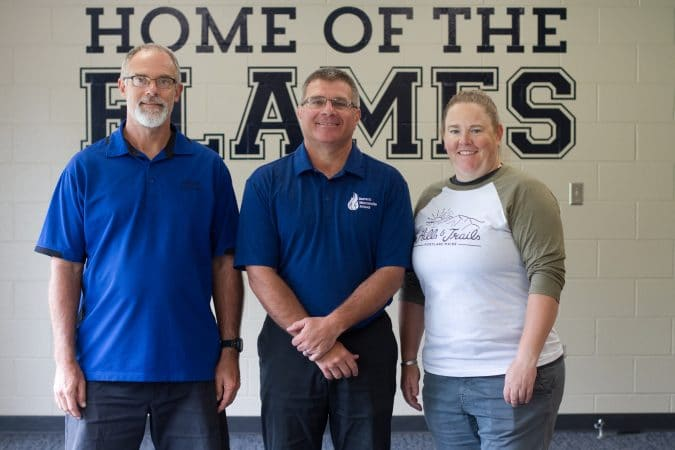 """Kendal Bauman (left) and Jennifer Young (right), """"roasted"""" Dave Bechler, center, at a spring recognition dinner where Bechler was recognized for 23 years of service to EMS as athletic director."""