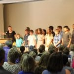 """Heidi Byler, grade 3, leads the group in singing, """"You are salt of the earth, oh people!"""""""