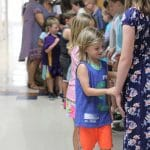 Graduates greet their classmates and teachers with a handshake