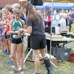 Katie Cimini hands award to the winner of the middle school race.