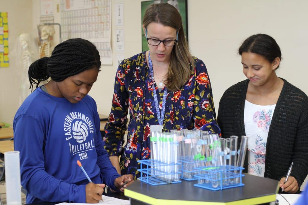 Science teacher Sarah Mitch with eighth grade students measuring volume and weight of materials gathered in the playground.