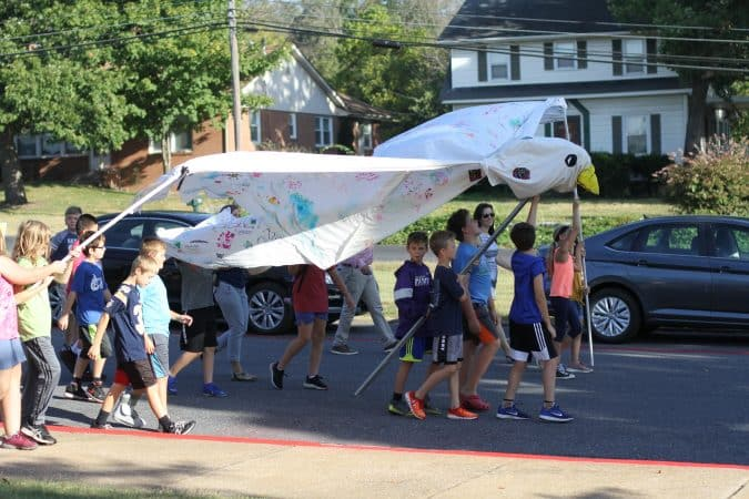 Fifth graders lead the 2019 Peace Parade with a dove puppet the school has used for 15 years.