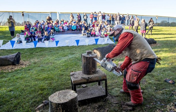 Local chainsaw artist Sean Haifee carves a jack-o-lantern out of a log during the demonstration for students at EMES. Photo by Daniel Lin/DN-R