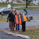 Mrs. Archer and fifth grade traffic helpers greet people in the new drop off loop