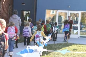 Students taking supplies to the new building.