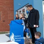 Paul Leaman, head of school, holds the  microphone for fifth grader Marlowe Nichols as she shares reflections.
