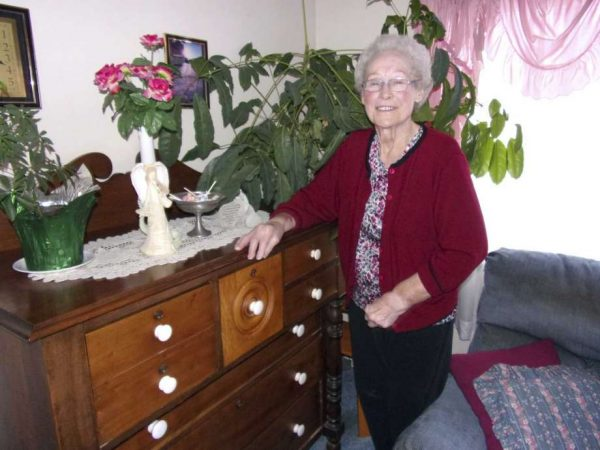 Freda Maust poses for a photo next to her century-old bureau that was made by her grandfather. (Rich Harp/For the Tribune)
