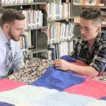 Justin King, high school principal, and Jal Ressler Horst '21, knot a comforter in the library.