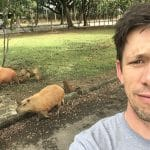 Andrew Jenner self portrait with some capybaras in Sao Paulo, Brazil, in June 2018, while reporting a story about birds and bird watching activism in the city for Birding magazine.