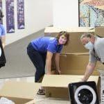 Shannon Roth, Anna Harrar and Jennifer Young unpack air filters for classroom air quality, COVID-19 era