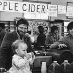 Keith and Eric Helmuth at their Farm Market stall with a young customer, 1982