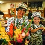 Ellen Helmuth at her Farm Market stall with granddaughter, Julia, 1997. Julia is pleased with having just made a sale of cut flowers.