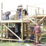 """""""Fleet of helpers"""" constructing multi-level, multi-tier stage to accommodate the required 10-foot distancing."""