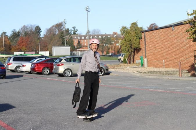 Curt Stutzman arrives for a day at work on his OneWheel, tie flying...