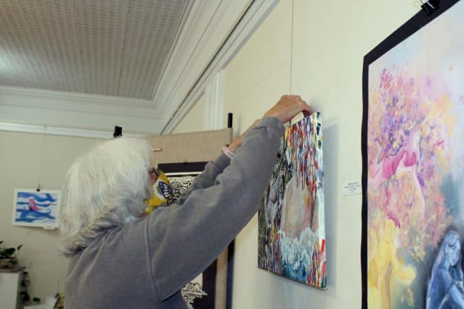 OASIS Fine Art and Craft member Sarah Lock hangs student art for he First Friday exhibition at the gallery in Harrisonburg. Photo by Kathleen Shaw/DN-R