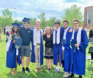 Maria Archer (center), K-8 principal, with '21 graduates who attended EMES