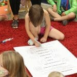 Kindergarten students take turns signing the peace pledge, 2021